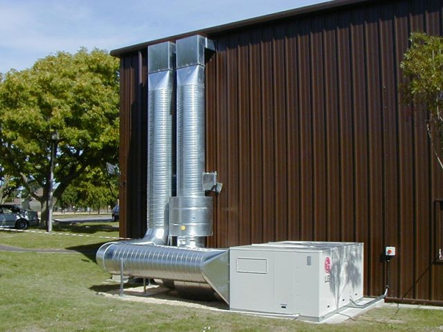 A large commercial ventilation system on the side of a warehouse