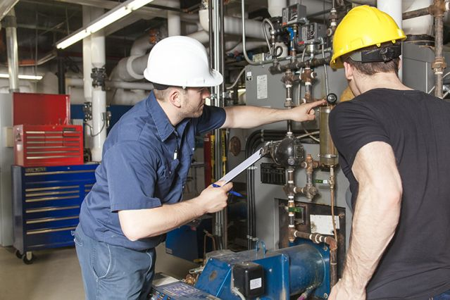 Two engineers servicing an HVAC system